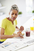 Mature Woman Eating Breakfast — Stock Photo