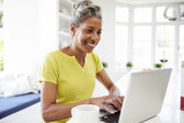 Woman Using Laptop In Kitchen — Stock Photo