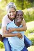 Mature Man Giving Woman Piggyback — Stock Photo