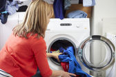 Woman Loading Clothes Into Washing Machine — Photo
