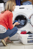 Woman Loading Clothes Into Washing Machine — Stok fotoğraf