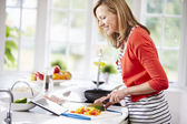 Woman In Kitchen Following Recipe — Stock Photo