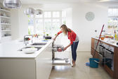 Woman Loading Plates Into Dishwasher — Stok fotoğraf