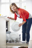 Woman Loading Plates Into Dishwasher — 图库照片