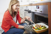 Woman Putting Tray Of Roast Vegetables — Stock Photo