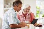 Middle Aged Couple Looking At Digital Tablet — Stock Photo