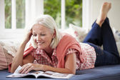 Woman Reading Magazine Lying On Sofa — Stock Photo