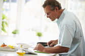 Man Following Recipe On Digital Tablet — Stock Photo