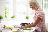 Woman Following Recipe On Digital Tablet — Stock Photo