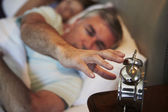 Man Reaching To Switch Off Alarm Clock — Stok fotoğraf