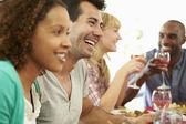Vrienden zitten rond de tafel te eten — Stockfoto