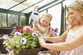 Mother And Daughter Watering Plants — Stock Photo