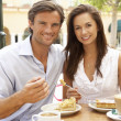 Young Couple Enjoying Coffee And Cake In Caf — Zdjęcie stockowe #4842822