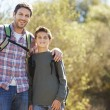 Father And Son Hiking In Countryside Wearing Backpacks — Stock Photo #48459129