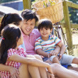 Asian Family Resting By Fence — Stock Photo #48459955