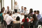 Businesswoman Addressing Meeting Around Boardroom Table — Stock Photo