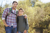 Father And Son Hiking In Countryside Wearing Backpacks — Photo