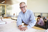 Male Architect Studying Plans In Office — Stock Photo