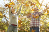 Couple Throwing Autumn Leaves In The Air — Stock Photo
