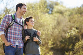 Father And Son Hiking In Countryside Wearing Backpacks — Stockfoto