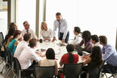 Zakenman adressering vergadering rond directiekamer tafel — Stockfoto