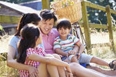 Asian Family Resting By Fence — Stockfoto