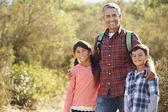Pai e filhos que caminham em campo vestindo mochilas — Foto Stock