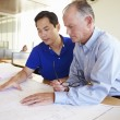 Architects Studying Plans In Modern Office Together — Stock Photo #48460819