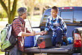 Father And Son Unpacking Truck On Camping Holiday — Стоковое фото
