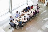 Zakenvrouw adressering vergadering rond directiekamer tafel — Stockfoto