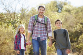 Father And Children Hiking In Countryside Wearing Backpacks — Foto Stock
