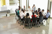 Businessman Addressing Meeting Around Boardroom Table — Stock Photo