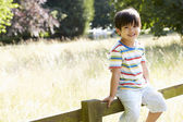 Asian Boy Sitting On Fence In Countryside — Stock Photo