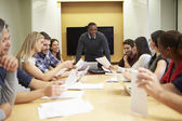Male Boss Addressing Meeting Around Boardroom Table — Stock Photo