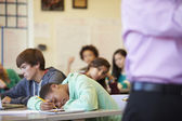 Bored High School Pupil Slumped On Desk — Stock Photo
