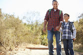 Father And Son Hiking In Countryside Wearing Backpacks — Stok fotoğraf