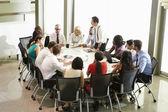 Businessman Addressing Meeting Around Boardroom Table — Stock Photo
