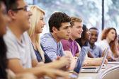 Třída studentů na vysokých pomocí přenosných počítačů v přednášce — Stock fotografie