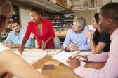 Female Boss Leading Meeting Of Architects Sitting At Table — Stock Photo