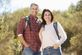Portrait Of Couple Hiking In Countryside Wearing Backpacks — Stok fotoğraf