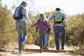 Rear View Of Family Hiking In Countryside Wearing Backpacks — Stock Photo