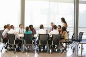Businesswoman Addressing Meeting Around Boardroom Table — Stockfoto