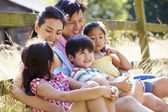 Asian Family Relaxing By Gate — Stock Photo