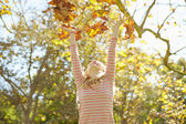 Young Girl Throwing Autumn Leaves In The Air — ストック写真