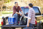 Two Men Unpacking Pick Up Truck On Camping Holiday — Stock Photo