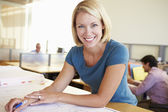 Female Architect Studying Plans In Office — Foto Stock