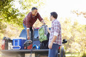 Two Men Unpacking Pick Up Truck On Camping Holiday — Stockfoto