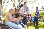 Two Girls Using Mobile Phone On Family Camping Holiday — Stock Photo