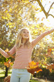 Young Girl Throwing Autumn Leaves In The Air — Stock Photo