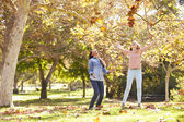 Two Girls Throwing Autumn Leaves In The Air — Stock Photo
